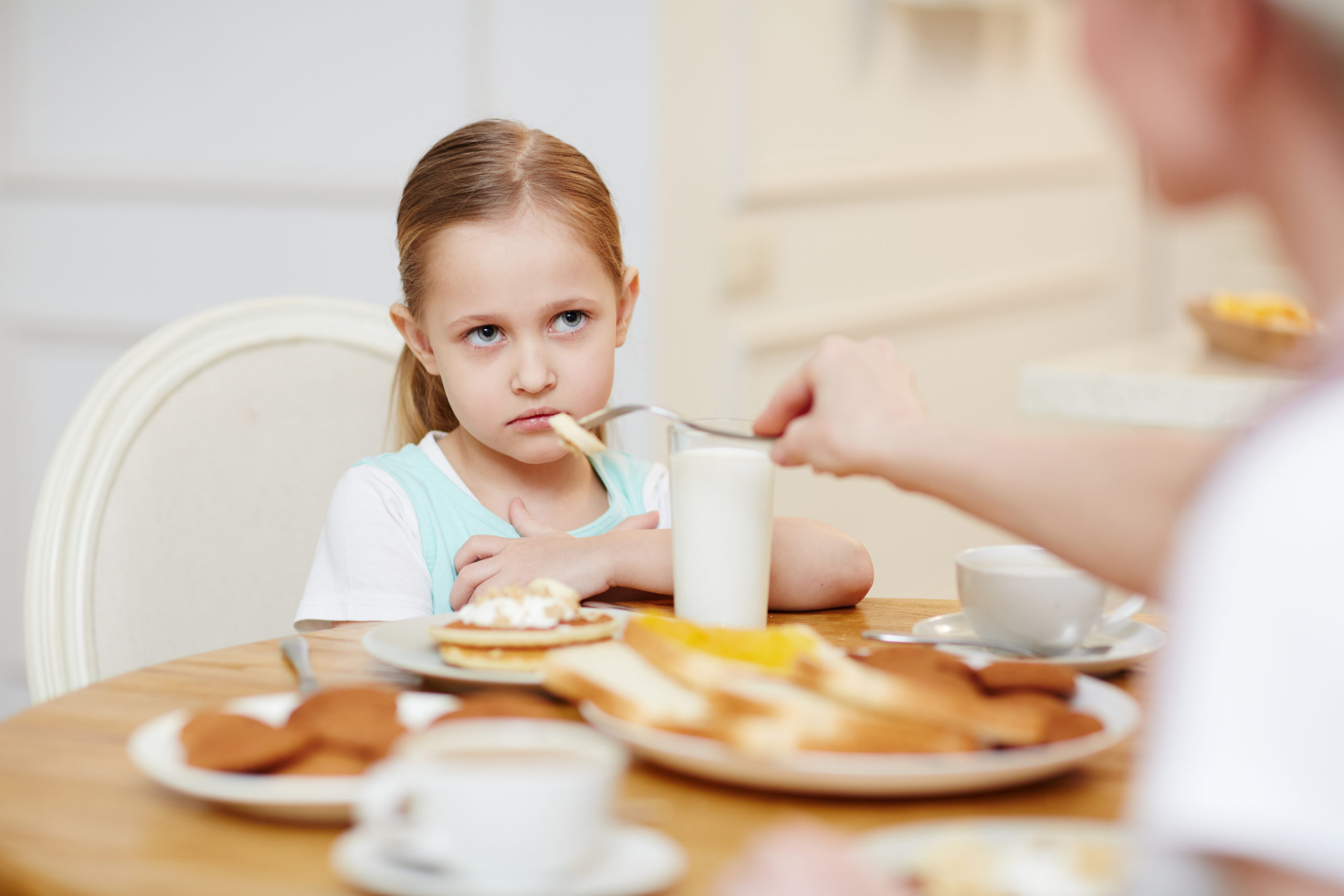 Angry displeased furrowed girl looking with grudge while refusing to eat when her mother feeding her with fork